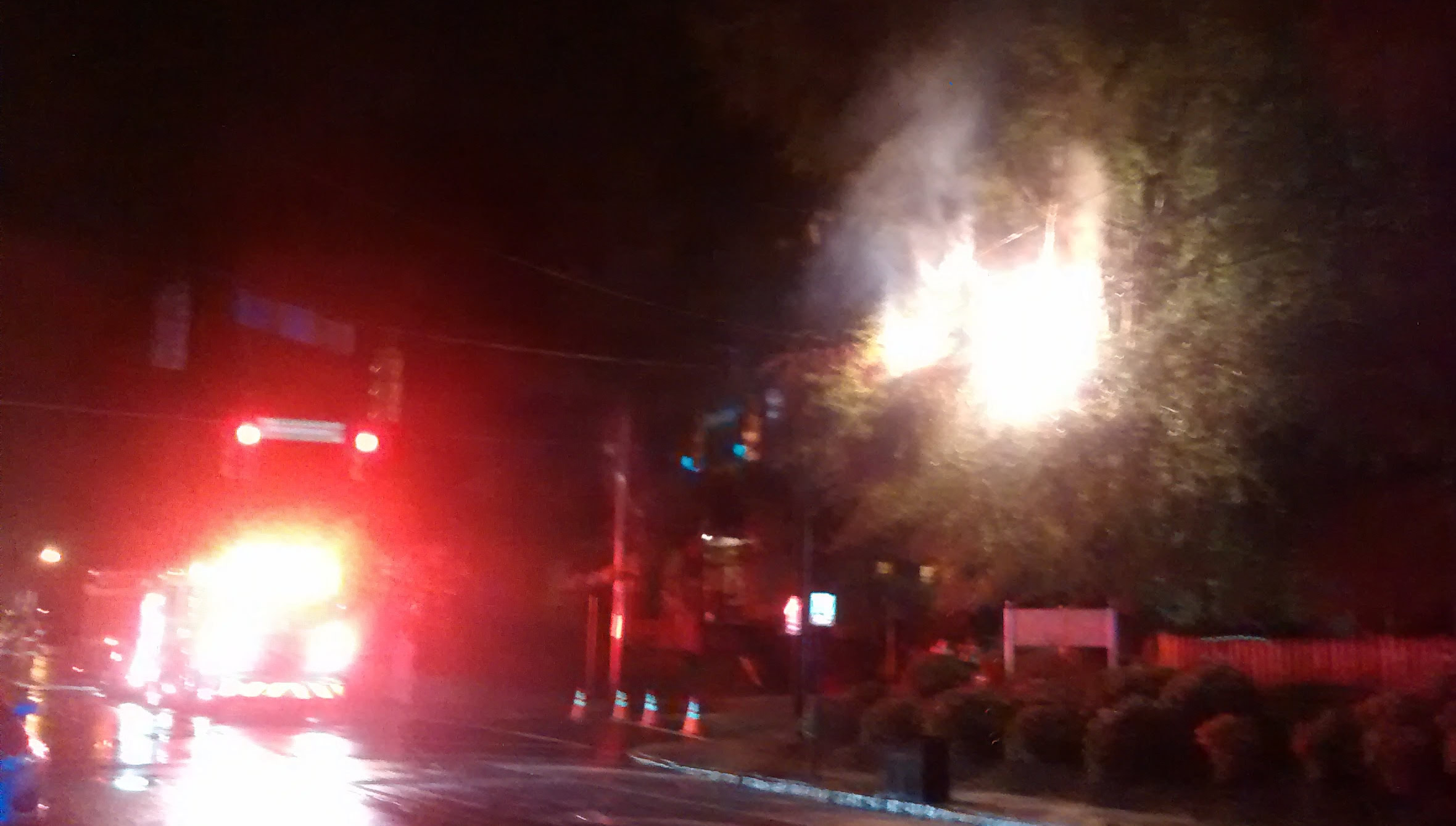 A blown transformer, a burning tree and a fire truck light up the rainy evening on Spring Garden Street.