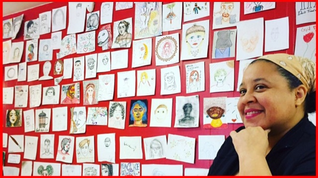 Karen and a wall with many small drawings of women