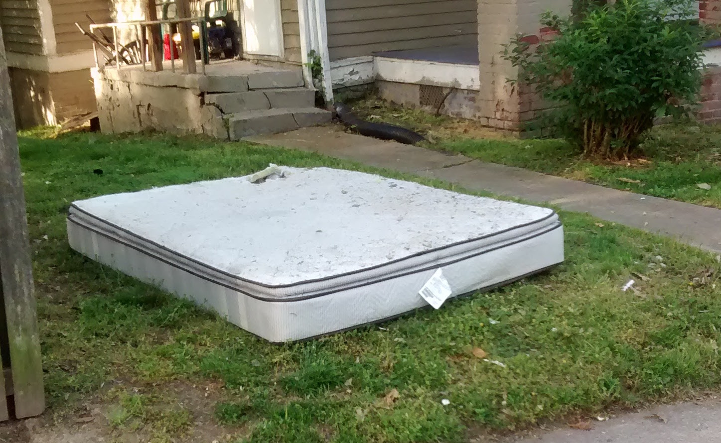 mattress in yard, thrown away by some thoughtless person
