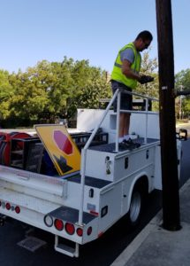 city workerer installing new traffic signs on Mendenhall Street