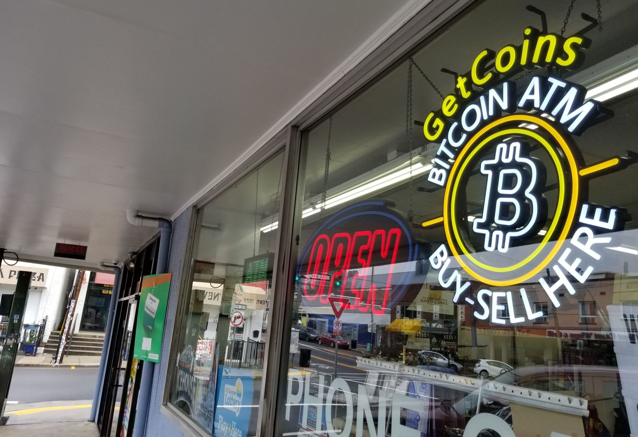 window of the College Mart woth neon Bitcon ATM sign